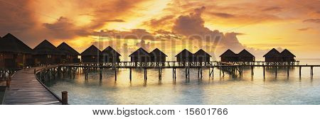 Beautiful panorama of tropical sunset with water villas