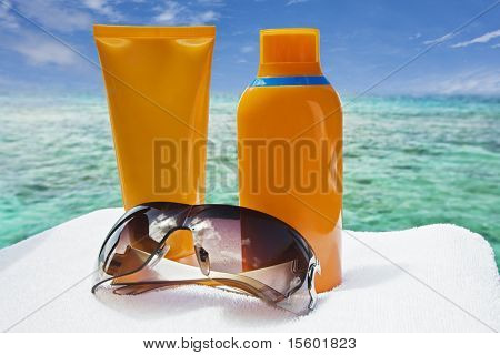 Sunglasses and sun-protection cream. Ocean on background