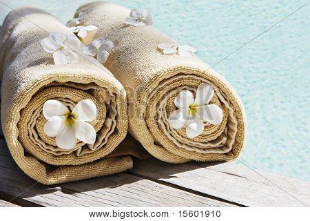 Toallas decoración con flores tropicales cerca de la piscina
