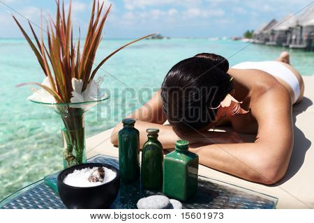 Beautiful woman getting spa treatment at daylight near the ocean. Focus on woman