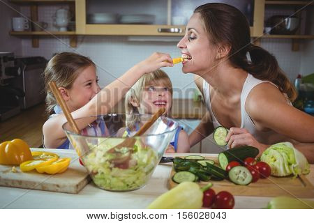 Kids feeding a slice of yellow bell pepper to mother in kitchen at home