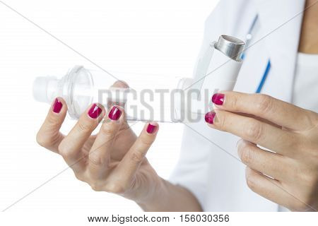 Close up of the hands of a female doctor holding a pressurized cartridge inhaler placed on an inhalation chamber on a medical demonstration - Isolated on a white background