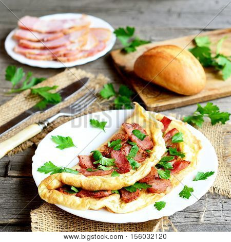 Delicious bacon omelette. Omelette stuffed with bacon and parsley on a plate, bacon slices on a plate, bread roll, fork, knife, chopping board, fresh parsley on old wooden background. Homemade cuisine