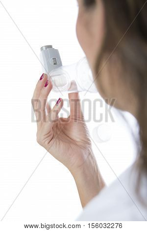 Woman is inhaling the medicament from the pressurized cartridge inhaler placed on an inhalation chamber - Rear view - Isolated on a white background