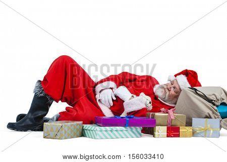 Santa claus sleeping beside christmas present against white background