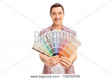 Happy young man holding a color swatch isolated on white background