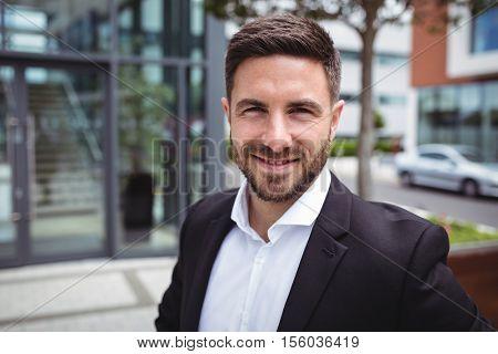Portrait of smiling businessman in office premises