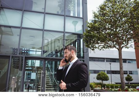 Businessman text messaging on mobile phone in office premises