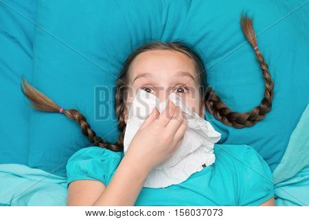 Girl with pigtails lying in bed and blowing his nose into a handkerchief. View from above