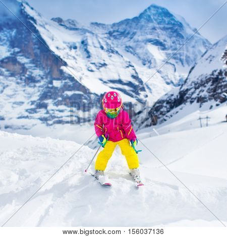 Child skiing in mountains. Active toddler kid with safety helmet goggles and poles. Ski race for young children. Winter sport for family. Kids ski lesson in alpine school. Little skier racing in snow