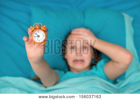 Girl shows at arm's length alarm clock and holding his head. View from above