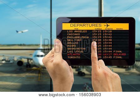 Hand holding tablet with connect wifi on the airport and see departures board