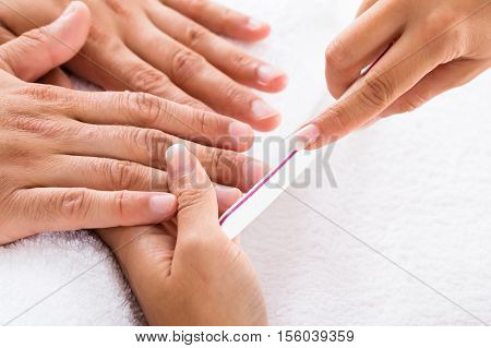 Close-up Of A Manicurist Filing Person's Nails In Salon