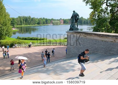 TSARSKOYE SELO, SAINT - PETERSBURG, RUSSIA - JULY 25, 2016: People climb stairs of Cameron Gallery Ensemble near Hercules Statue. On the background is Great Pond and Admiralty Pavilion