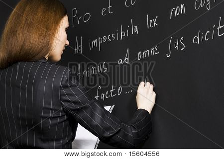 Young teacher writing legal proverbs in latin language