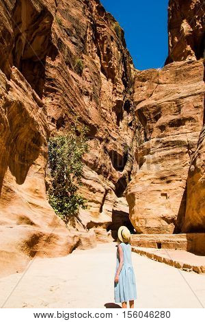 Photo of the Stylish female tourist in trendy hat and sky-blue dress explore canyon Siq leading to The Treasury, Al Khazneh. Travel and adventure concept.