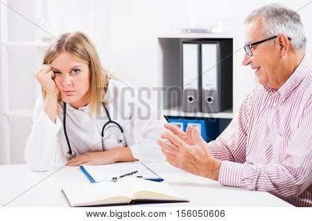 Doctor is getting bored while hypochondriac patient is explaining his health problems.