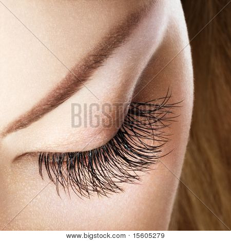 Woman eye with extremely long eyelashes without makeup.