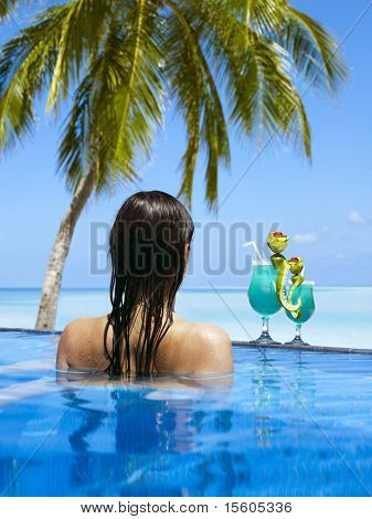Woman enjoying sunny day at the swimming pool near the ocean