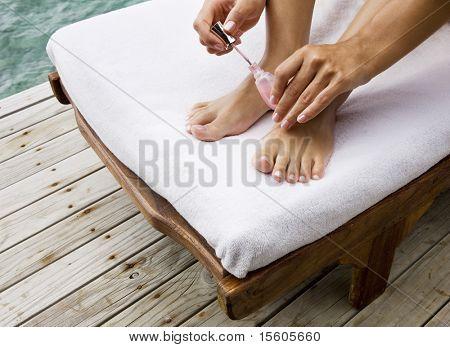 Closeup of female feet and hands. Beauty treatment otdoors