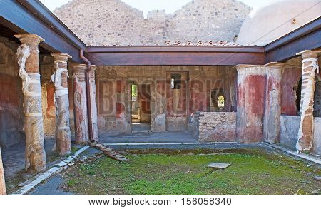 The ancient courtyard of the Roman villa with painted walls and columns Pompeii Italy.