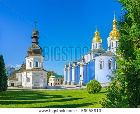 The old Refectory of St John the Divine and painted Cathedral of St Michael's Golden-Domed Monastery surrounded by green garden Kiev Ukraine.