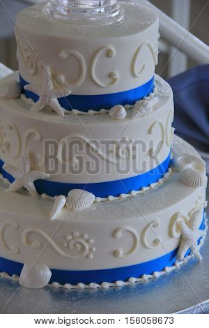 Delicious three-tier wedding cake in seashore theme, set on table at reception.