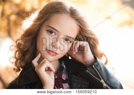 Beautiful teen girl 12-14 year old wearing casual stylish clothes posing outdoors. Looking at camera. Autumn season.