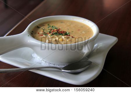 White bowl with hot,steaming, corn seafood chowder on table