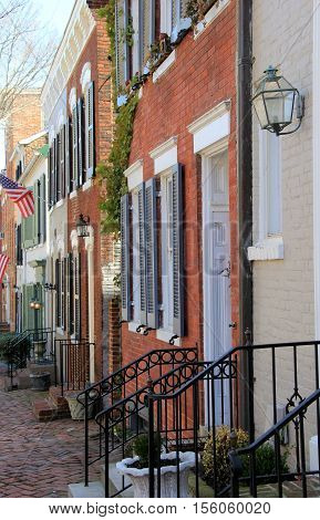 Several row houses lining neat and orderly neighborhood street.