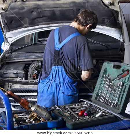 auto mechanic repairing a car engine. Different work tools on foreground.