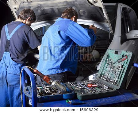 auto mechanics repairing a car engine. Different working tools on foreground