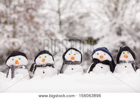 Five cute snowmen dressed for winter all facing forward and sat on snow. Snowmen wearing hats and scarfs with carrot noses. Winter scene in the background with trees covered.