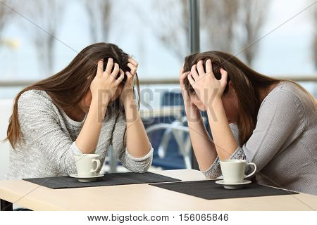 Two desperate sad girls crying with hands over head in a bar with a window with a winter background
