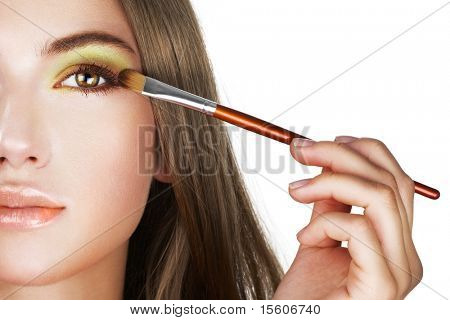 Beautiful woman applying colorful eye makeup