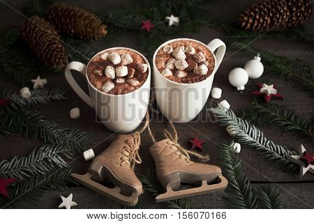 Two cups of hot cocoa or hot chocolate with marshmallows with fir tree and skates, traditional beverage for winter time. Christmas concept.