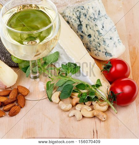 Glass of white wine with cheese nuts and tomatoes on a wooden plate