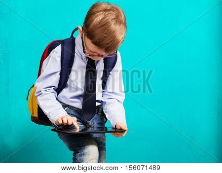 Cheerful Little Boy With Big Backpack Holding Digital Tablet Against Blue Background.