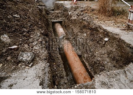 Rusty water pipe in the trench ground overhead view. Repairing of the water delivery system. Open trench with water pipe and heap of ground near. Industrial plumbing concept.
