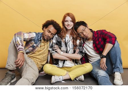Two exhausted young men sleeping on shoulders of happy woman over yellow background