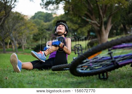 Female cyclist getting injured while falling from mountain bike in park