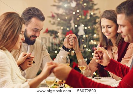 Picture showing group of friends praying over Christmas table