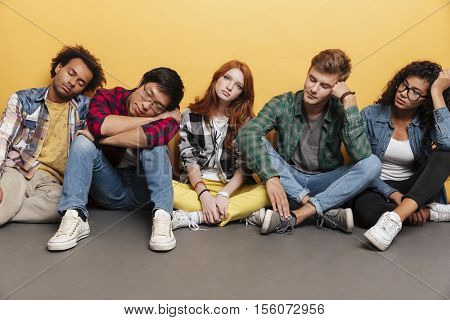 Group of tired young people sitting and sleeping over yellow background