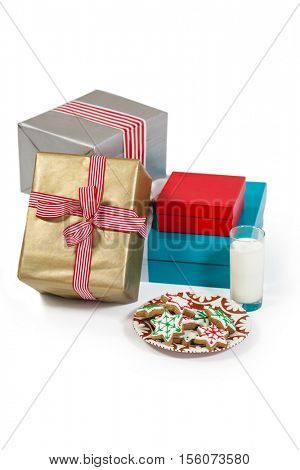 Close-up of milk and sweet food in plate with wrapped gift against white background