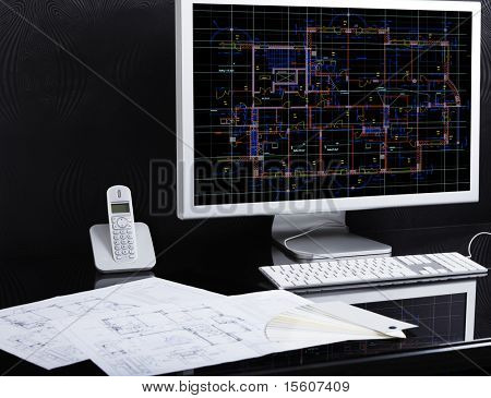 Work place of architect. Architectural project on computer monitor. Blueprints on the desk.