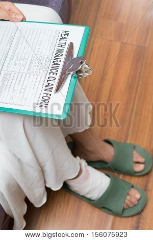 lady with a hurted foot about to fill a health insurance claim form at home