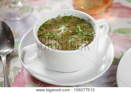 Chicken Broth With Greens In A White Cup