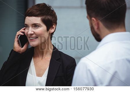 Businesswoman talking on mobile phone in office premises