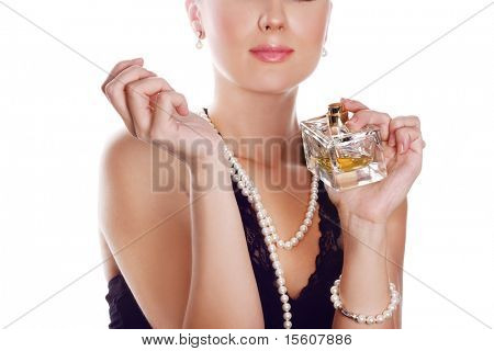 Woman in classic style applying perfume on her wrest. Focus on hands and bottle.