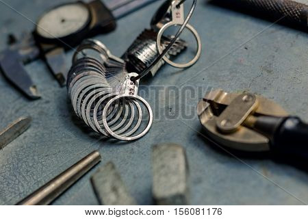 Tools Set Of Jewellery. Jewelry Workplace On Metal Background. Finger Sizing For Rings, Beam Compass